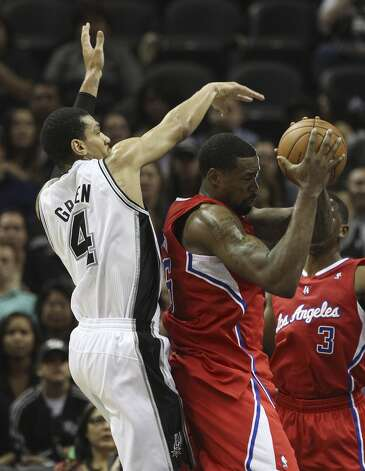 Spurs' Danny Green (04) attempts to swat the ball away from Los Angeles Clippers' DeAndre Jordan (06) in the first half of their game at the AT&T Center on Monday, Nov. 19, 2012. (Kin Man Hui / San Antonio Express-News)