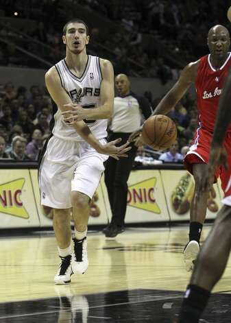Spurs' Nando De Colo (25) makes a pass against the Los Angeles Clippers in the first half of their game at the AT&T Center on Monday, Nov. 19, 2012. (Kin Man Hui / San Antonio Express-News)