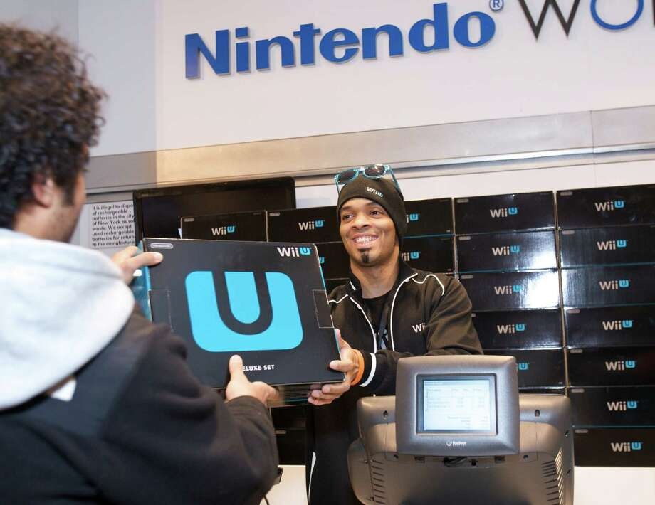 In this photo provided by Nintendo of America, a fan purchases one of the first Wii U systems in the world at the midnight launch event at Nintendo World in New York on Sunday Nov. 18, 2012. Wii U is set to change the way people interact with their games, their TVs and each other. (AP Photo/Nintendo, Anders Krusberg) Photo: Anders Krusberg, HOEP / Nintendo of America