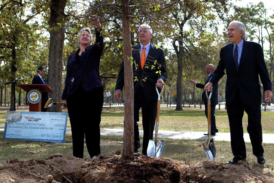 Mayor Annise Parker, left; chairman of the Memorial Park Conservancy Jim Porter, center, and Houston Livestock Show Chairman Steve Stevens Jr., take the first step toward planting new trees at Memorial Park. Photo: Cody Duty, Staff / © 2012 Houston Chronicle