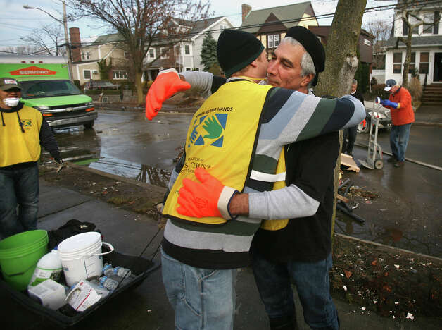 Mormon volunteer Matt Maddox, left, of Stamford, gets a hug from homeowner Al Zirino as four busloads from the Church of Jesus Christ of Latter Day Saints participate in the Hurricane Sandy relief effort in the Far Rockaway section of Queens, NY, on Sunday, November 18, 2012. Photo: Brian A. Pounds / Connecticut Post