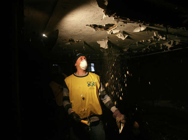 Mormon volunteer Matt Maddox, of Stamford, tears down a water logged basement ceiling during Hurricane Sandy relief efforts in the Far Rockaway section of Queens, NY, on Sunday, November 18, 2012. Photo: Brian A. Pounds / Connecticut Post