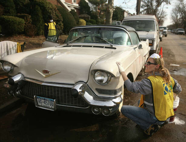 Mormon volunteer Amy Huling, of Pleasantville, NY, washes a 1957 Cadillac flooded during Hurricane Sandy in the Far Rockaway section of Queens, NY, on Sunday, November 18, 2012. Photo: Brian A. Pounds / Connecticut Post