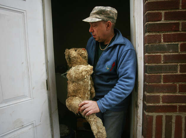 Far Rockaway homeowner Kurt Schneck holds together an antique Steiff teddy bear damaged by Hurricane Sandy flooding, on Sunday, November 18, 2012. Photo: Brian A. Pounds / Connecticut Post