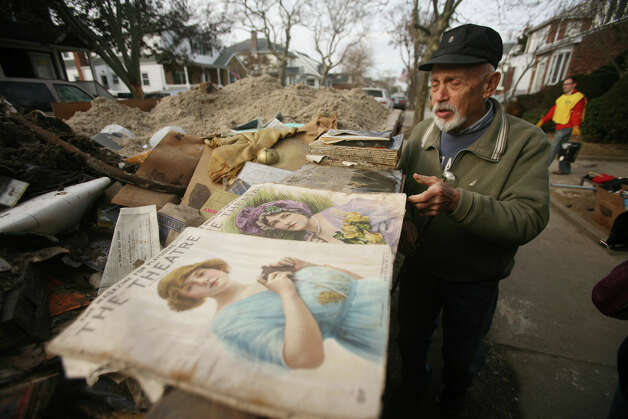 Homeowner Ed Schneck tries to salvage antique magazines that were removed from his basement during Hurricane Sandy relief efforts in the Far Rockaway section of Queens, NY, on Sunday, November 18, 2012. Photo: Brian A. Pounds / Connecticut Post