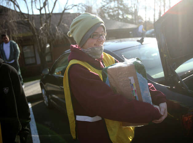 Mormon volunteer Lynnea Aillery, of Stamford, carries a case of water as the Hurricane Sandy relief effort departs for the Far Rockaway section of Queens, NY, on Sunday, November 18, 2012. Photo: Brian A. Pounds / Connecticut Post