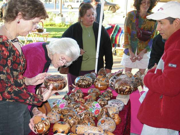 Customers examine an artisan's wares at the International Peace Market. Photo: Courtesy, Esperanza Peace And Justice Center