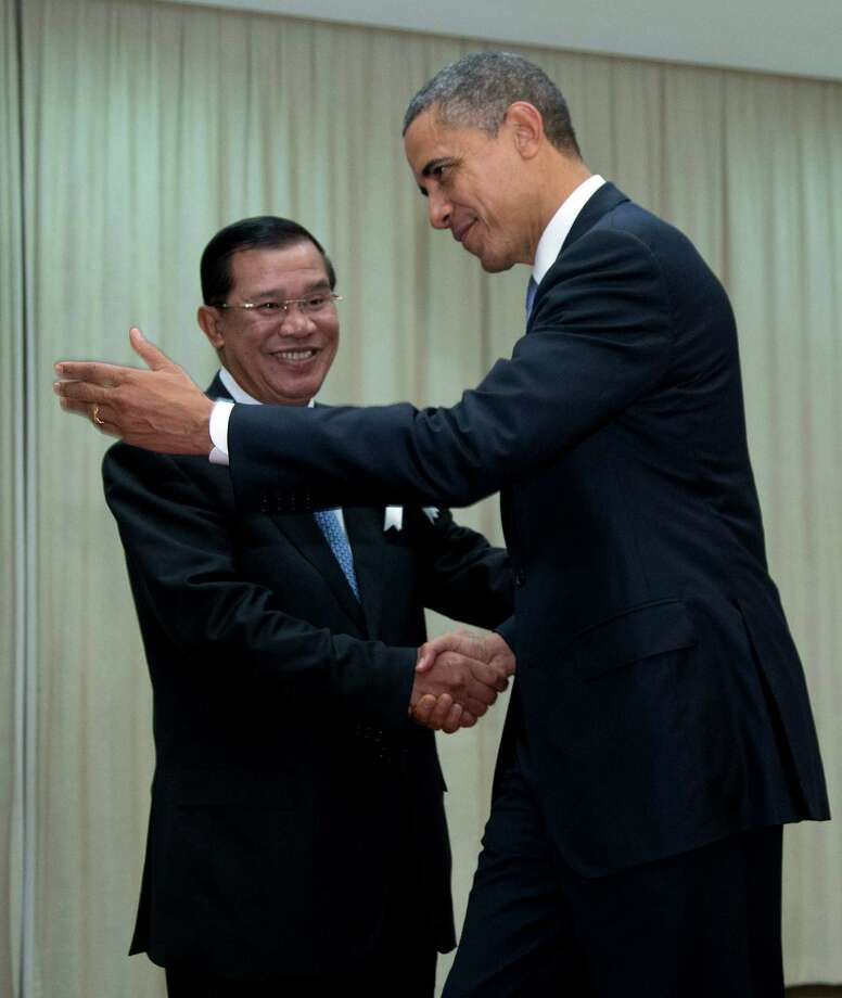 U.S. President Barack Obama is welcomed by Cambodia's Prime Minister Hun Sen as he arrives at the Peace Palace in Phnom Penh, Cambodia, Monday, Nov. 19, 2012. Obama will attend the East Asia Summit.  (AP Photo/Carolyn Kaster) Photo: Carolyn Kaster