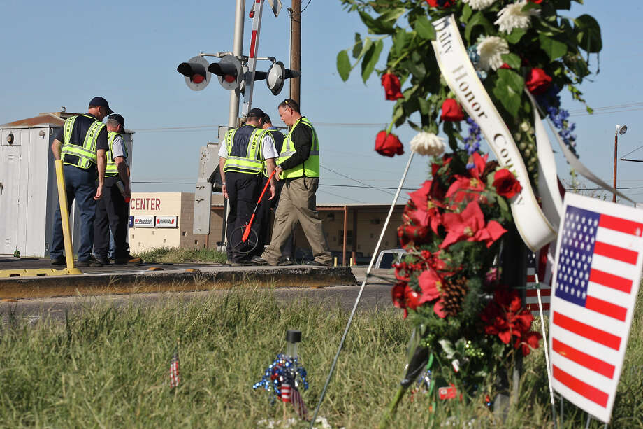 Workers inspect the intersection in Midland where a Union Pacific train struck a float carrying veterans, killing four men. Photo: Edward A. Ornelas, Staff / © 2012 San Antonio Express-News