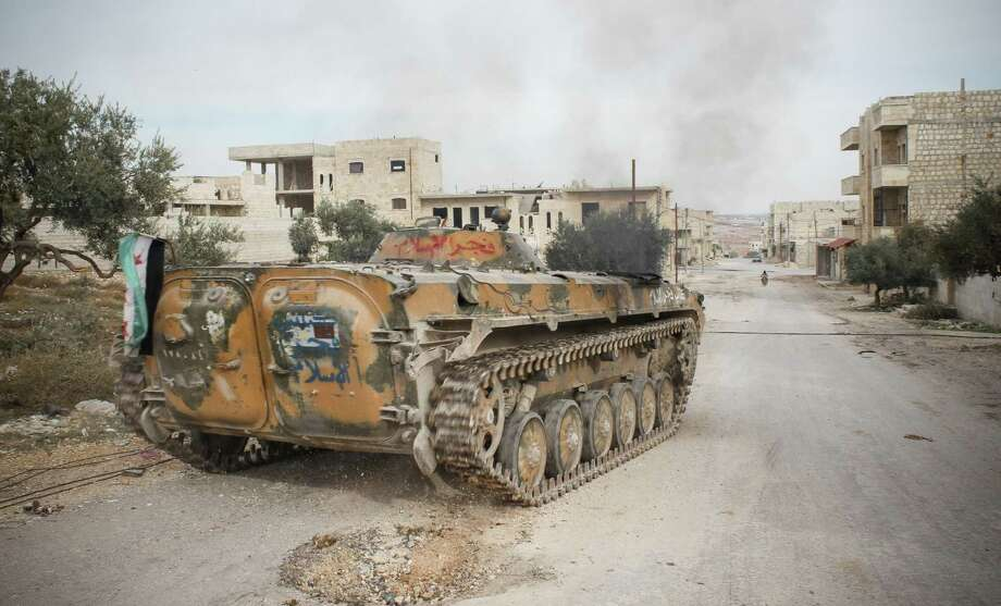 An armored vehicle acquired from the Syrian army during the course of the bloody civil war and flying the Syrian revolutionary flag rumbles down a main street in the northwestern city of Maraat al-Numan, Syria. Photo: Mustafa Karali, STR / AP2012