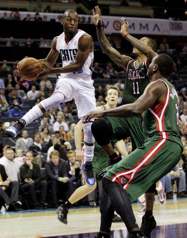 Charlotte Bobcats' Kemba Walker, left, looks to pass as Milwaukee Bucks' Monta Ellis, center, and Samuel Dalembert, right, defend during the first half of an NBA basketball game in Charlotte, N.C., Monday, Nov. 19, 2012. (AP Photo/Chuck Burton) Photo: Chuck Burton
