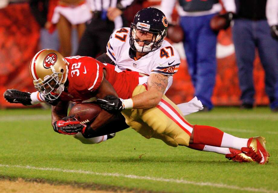Running back Kendall Hunter (32) is tackled by Chicago safety Chris Conte (47) in the first half of the San Francisco 49ers game against the Chicago Bears at Candlestick Park in San Francisco, Calif., on Monday November 19, 2012. Photo: Carlos Avila Gonzalez, The Chronicle / ONLINE_YES