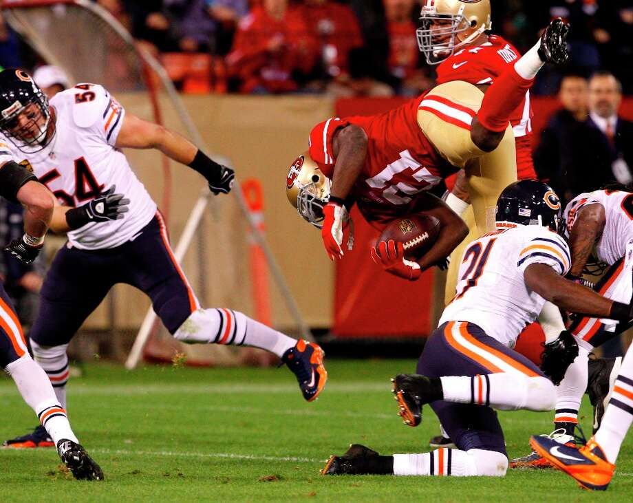Running back Frank Gore (21) flies through the air after a tackle in the first half of the San Francisco 49ers game against the Chicago Bears at Candlestick Park in San Francisco, Calif., on Monday November 19, 2012. Photo: Carlos Avila Gonzalez, The Chronicle / ONLINE_YES