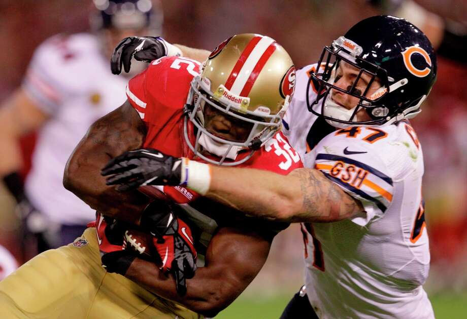 Running back Kendall Hunter (32) gets tackled by safety Chris Conte (47) during the first half of the the San Francisco 49ers game against the Chicago Bears at Candlestick Park in San Francisco, Calif., on Monday November 19, 2012. Photo: Stephen Lam, Special To The Chronicle / ONLINE_YES