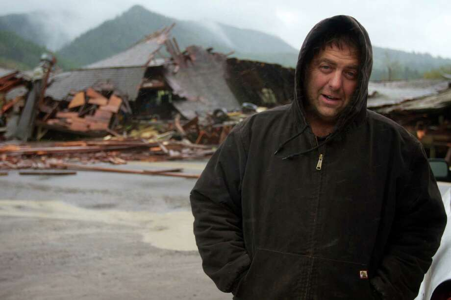 Gary Petty's stands in front of his 1930-vintage barn which collapsed across the Kilchis River Road, east of Highway 101 near Tillamook, Ore., after high high winds hit the Oregon coast on Monday, Nov. 19, 2012. Residents in Washington and Oregon are bracing for expected river flooding after heavy rain and winds that caused sporadic road closures, power outages and at least one death. The wet weather is expected to continue throughout the week, after hurricane-strength winds battered both states along the coast. Photo: AP