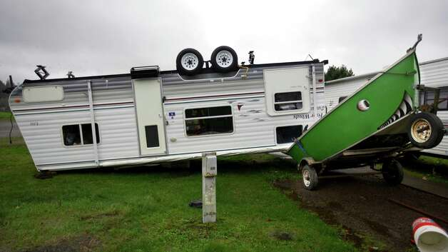 A camp trailer is left upside down at the Old Mill Marina trailer park in Garibaldi, Ore., after high winds and rain hit the Oregon coast on Monday, Nov. 19, 2012. The trailer was unoccupied when it flipped. Residents in Washington and Oregon are bracing for expected river flooding after heavy rain and winds that caused sporadic road closures, power outages and at least one death. The wet weather is expected to continue throughout the week, after hurricane-strength winds battered both states along the coast. (AP Photo/The Oregonian, Randy L. Rasmussen)  MAGS OUT; TV OUT; LOCAL TV OUT; LOCAL INTERNET OUT; THE MERCURY OUT; WILLAMETTE WEEK OUT; PAMPLIN MEDIA GROUP OUT Photo: AP