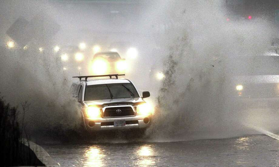 Traffic plows through high water as it merges onto Interstate 5 in Portland, Ore., Monday, Nov. 19, 2012. A powerful storm is pounding the Oregon coast, shutting down marine traffic in and out of several coastal rivers and closing part of highway U.S. 101. Photo: AP