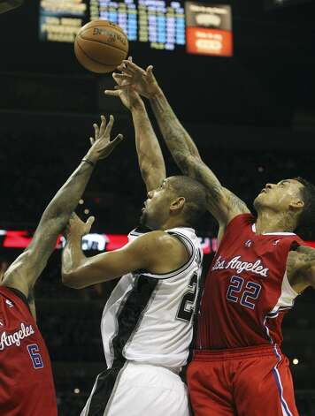 Spurs' Tim Duncan (21) attempts a shot between Los Angeles Clippers' DeAndre Jordan (06) and Matt Barnes (22) in the second half of their game at the AT&T Center on Monday, Nov. 19, 2012. Clippers defeated the Spurs, 92-87. (Kin Man Hui / San Antonio Express-News)