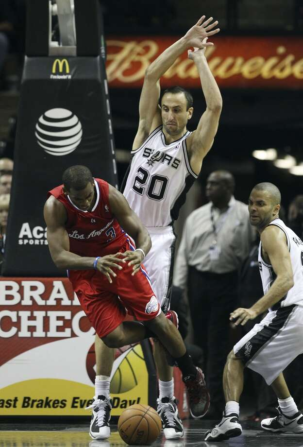 Los Angeles Clippers' Chris Paul (03) get tripped up while driving between Spurs' Manu Ginobili (20) and Tony Parker (09) in the second half of their game at the AT&T Center on Monday, Nov. 19, 2012. Clippers defeated the Spurs, 92-87. (San Antonio Express-News)