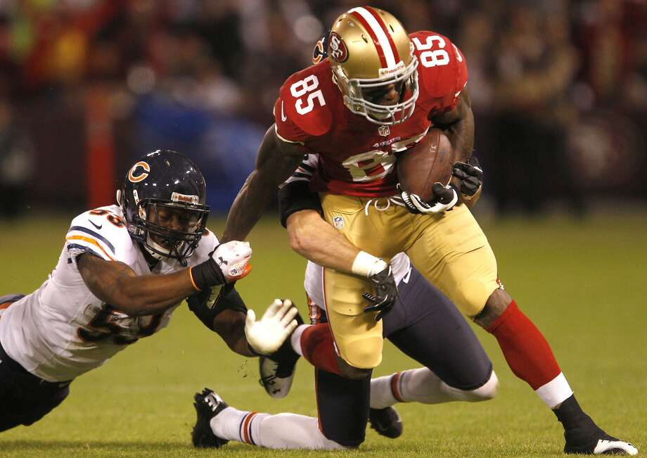 Tight end Vernon Davis (85) runs through a  tackle by linebacker Nick Roach (53) in the first half of the San Francisco 49ers game against the Chicago Bears at Candlestick Park in San Francisco, Calif., on Monday November 19, 2012. Photo: Carlos Avila Gonzalez, The Chronicle