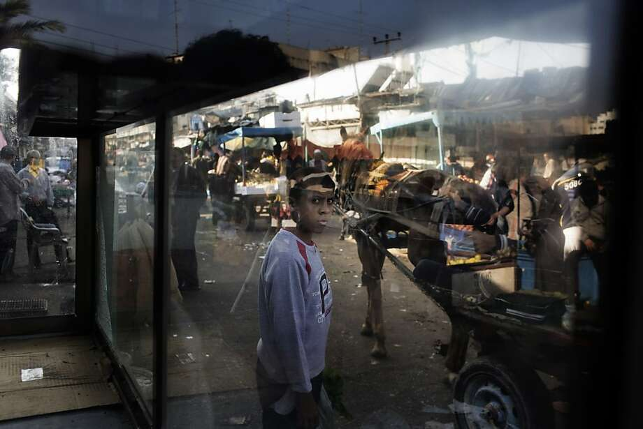 A Palestinian boy is seen through a glass booth at a central market in Gaza City on November 19, 2012. Food prices have started to rise in the Gaza Strip due to the lack of fresh supplies as scarce produce is met with more demands by the residents of the Palestinian coastal enclave, due to the ongoing unrest with Israel. Photo: Marco Longari, AFP/Getty Images