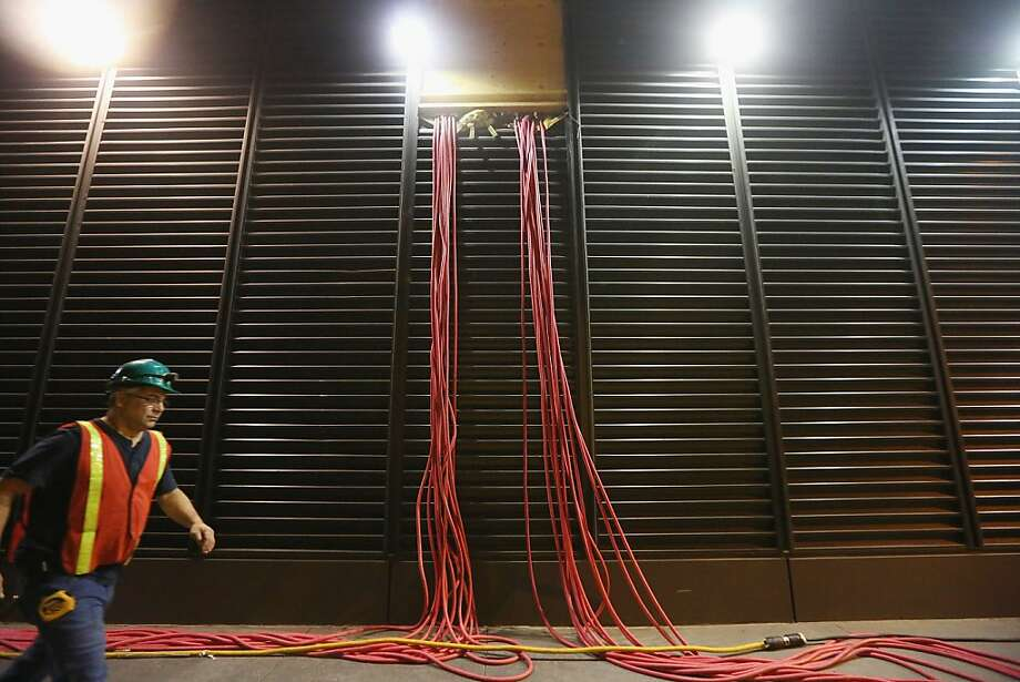 A worker walks past temporary cables running from generators into a Financial District building in an area that flooded during Superstorm Sandy on November 19, 2012 in New York City. Many of the office towers in the low lying Financial District which flooded remain closed due to damage to heating and electrical infrastructure.  Many other buildings in the area are being powered by generators. Photo: Mario Tama, Getty Images