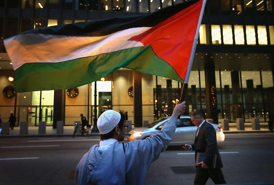 Abdur Rahman waves a Palestinian flag as he participates in a demonstration calling for an end to Israeli attacks on Gaza on November 19, 2012 in Chicago, Illinois. Several hundred protestors rallied in the Federal Building Plaza before marching through the Loop during rush hour. Photo: Scott Olson, Getty Images