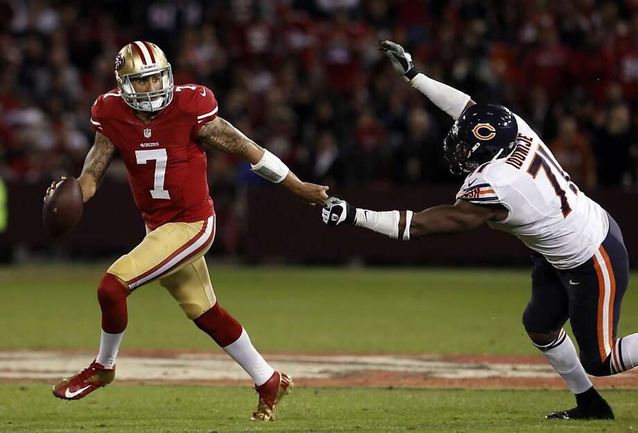 Colin Kaepernick scrambles in the fourth quarter under pressure from Israel Idonije. The San Francisco 49ers played the Chicago Bears at Candlestick Park in San Francisco, Calif., on Monday November 19, 2012, and won 32-7. Photo: Carlos Avila Gonzalez, The Chronicle