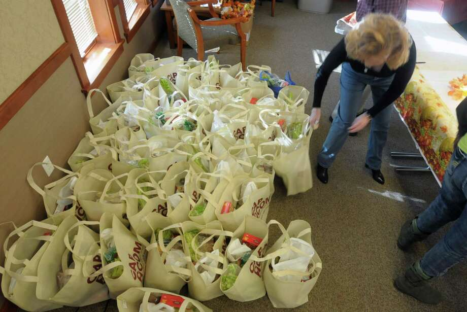 Volunteer Shari Kern of Troy grabs a food basket to give to a family during the Commission on Economic Opportunity for the Greater Capital Region Thanksgiving food basket program.  The organization increased the number of families by a third this year and are helping a total of 125 families.  Businesses such as Cap Com along with private donors and other area businesses made donations towards the food baskets.  The food basket program was started in the early 1990's and the organization also helps families out with food baskets for Chirstmas.  With all the different programs and services the organization offers they help over 14,000 people yearly through their food pantry, WIC program and YouthBuild to name a few.  (Paul Buckowski / Times Union) Photo: Paul Buckowski