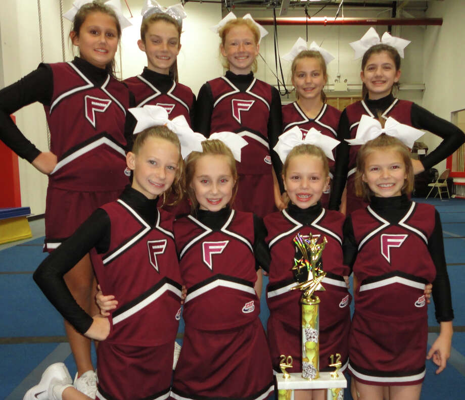 The Fairfield PeeWee Giants cheerleaders, with one of their several trophies, are raising money to travel to the Pop Warner National Championship at Disneyís Wide World of Sports Complex in Orlando, Fla., next month. Photo: Meg Barone / Fairfield Citizen freelance