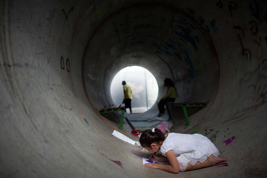 NITZAN, ISRAEL - NOVEMBER 19:  (ISRAEL OUT)  An Israeli child plays in a large concrete pipe used as a bomb shelter on November 19, 2012 in Nitzan, Israel. According to reports November 19, 2012, at least 90 Palestinians have been killed and more than 700 wounded during the Israeli offensive in the Gaza Strip. Photo: Uriel Sinai, Getty Images / 2012 Getty Images
