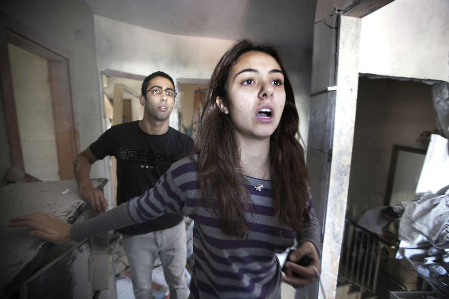Lotam Hakmon (R) and her brother (L) react as they survey the damage to their home after it was hit by a rocket launched by Palestinian militants from the Gaza Strip in the southern Israeli city of Beer Sheva on November 20, 2012. Israel put on hold its threatened Gaza ground offensive to give Egyptian-led truce talks a chance as top diplomats flew in to boost efforts to end nearly a week of cross-border violence. AFP PHOTO/MENAHEM KAHANA Photo: MENAHEM KAHANA, AFP/Getty Images / 2012 AFP