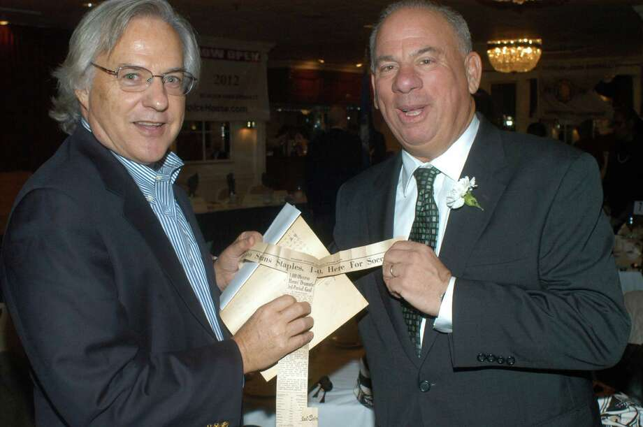 John Penberthy, left, and Wayne Mones, teammates and Brien McMahon class of 1970 alums, hold up a Stamford Advocate newspaper clipping from their 1969 FCIAC soccer championship win during the Norwalk Old Timers' Athletic Association Sports Awards Presentation at Continental Manor on Nov. 15. Mones, who scored the decisive goal in the game, was one of the Old Timers award recipients honored at the ceremony. Photo: Andy Hutchison