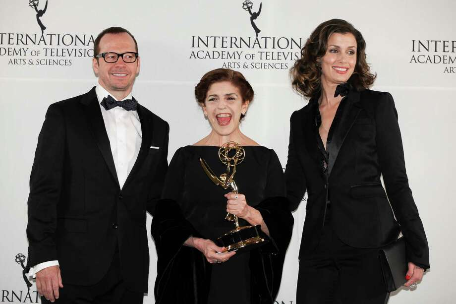 "This Nov. 19, 2012 photo released by Starpix shows Argentine actress Cristina Banegas, center, posing with presenters Donnie Wahlberg, left, and Bridget Moynihan after winning the Best Performance by an Actress award for her role in the miniseries ""Television por la Inclusion,"" at the 40th International Emmy Awards in New York. Photo: Andrew Toth, AP / STARPIX"