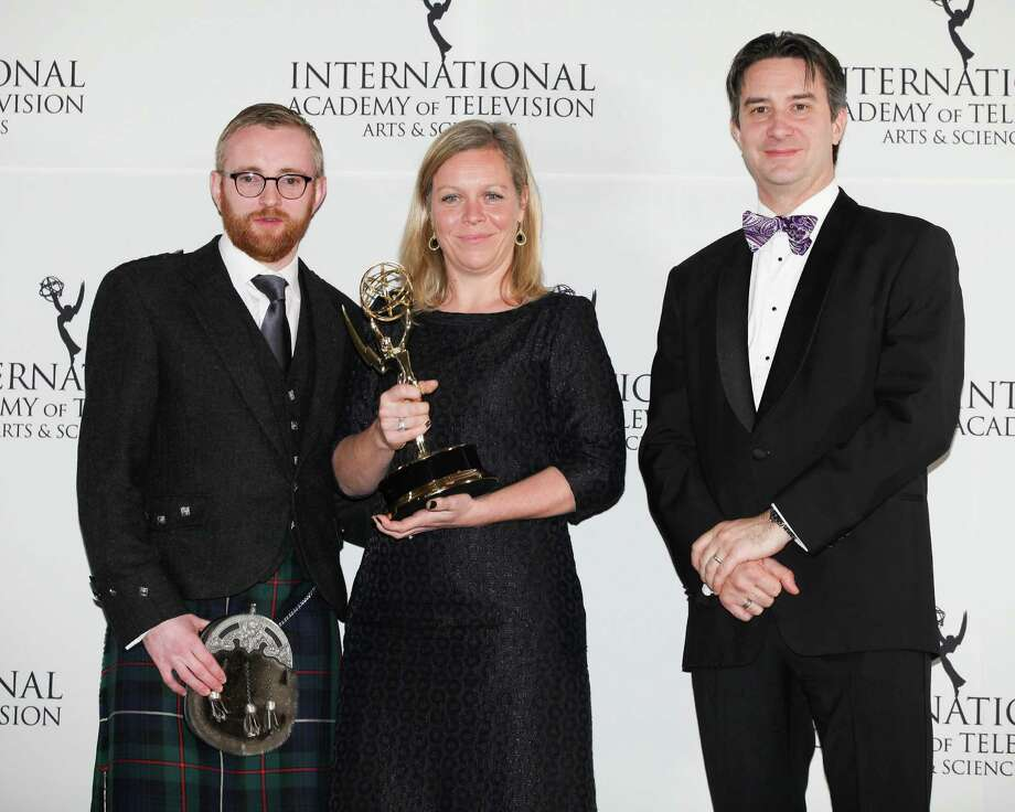 """This Nov. 19, 2012 photo released by Starpix shows Charlotte Moore, center, Craig Hunter, left, and Rob Wilkins after Moore and Hunter won the Documentary award for """"Terry Pratchett: Choosing to Die"""" at the 40th International Emmy Awards in New York. Wilkins was Pratchett's assistant. Photo: Andrew Toth, AP / STARPIX"""