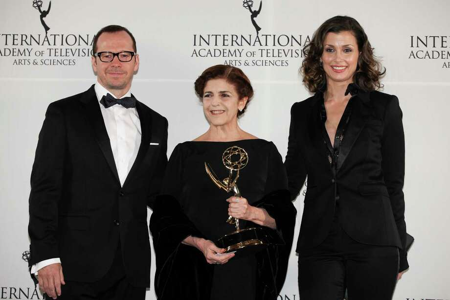 "This Nov. 19, 2012 photo released by Starpix shows Argentine actress Cristina Banegas, center, posing with presenters Donnie Wahlberg, left, and Bridget Moynihan after winning the Best Performance by an Actress award for her role in the miniseries ""Television por la Inclusion,"" at the 40th International Emmy Awards. Photo: Andrew Toth, AP / STARPIX"