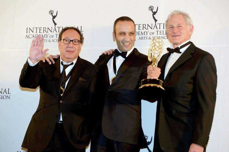 "Producer Claude Chelli, left, and writer Abdul Raouf Dafri, center, celebrate winning an International Emmy for Drama Series for ""Braquo"" with presenter Victor Garber at the 40th International Emmy Awards,  Monday, Nov. 19, 2012 in New York. Photo: Henny Ray Abrams, AP / FR151332 AP"