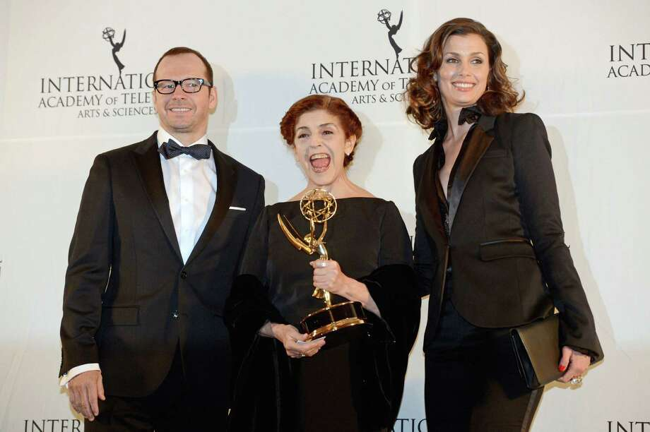 "Argentine actress Cristina Banegas, center, poses with presenters Donnie Wahlberg, left, and Bridget Moynihan after winning the Best Performance by an Actress award for her role in the miniseries ""Television por la Inclusion,"" at the 40th International Emmy Awards,  Monday, Nov. 19, 2012 in New York. Photo: Henny Ray Abrams, AP / FR151332 AP"