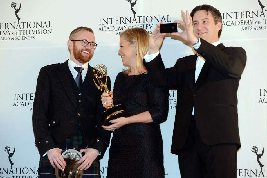 "Britons Charlotte Moore, center, and Craig Hunter, left, are joined by Rob Wilkins, also of Great Britain, after Moore and Hunter won the Documentary award for ""Terry Pratchett: Choosing to Die"" at the 40th International Emmy Awards,  Monday, Nov. 19, 2012 in New York. Wilkins was Pratchett's assistant. Photo: Henny Ray Abrams, AP / FR151332 AP"