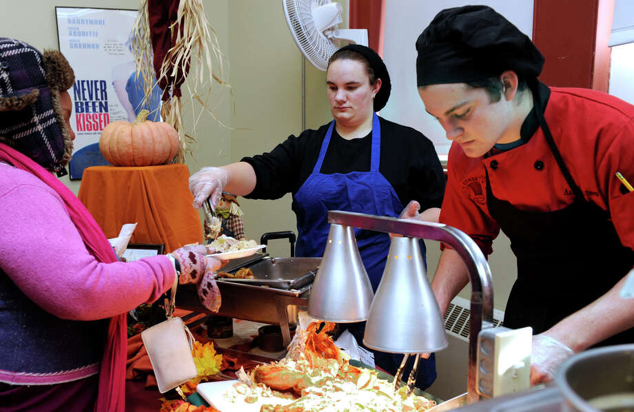 Mikayla Morrissey, 18, center, a student at ACE, and Aaron Boisvert, 17, a student at Abbott Tech, serve turkey at the annual Thanksgiving dinner for the community, Tuesday, Nov. 20, 2012. Photo: Carol Kaliff / The News-Times