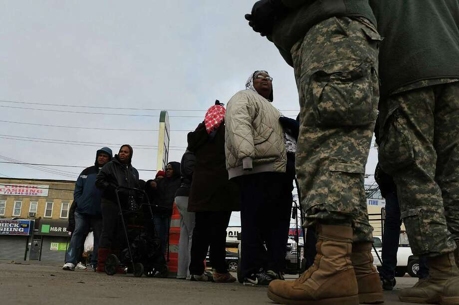 NEW YORK, NY - NOVEMBER 19:  Members of the U.S. Army Reserves help at a food distribution site in the heavily damaged Rockaway neighborhood, where a large section of the iconic boardwalk was washed away on November 19, 2012 in the Queens borough of New York City. Three weeks after Superstorm Sandy slammed into parts of New York and New Jersey, thousands are still without power and heat. Photo: Spencer Platt, Getty Images / 2012 Getty Images