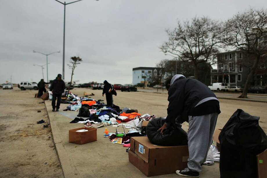 NEW YORK, NY - NOVEMBER 19: People look through donated clothes in a parking lot of the heavily damaged Rockaway neighborhood, where a large section of the iconic boardwalk was washed away on November 19, 2012 in the Queens borough of New York City. Three weeks after Superstorm Sandy slammed into parts of New York and New Jersey, thousands are still without power and heat. Photo: Spencer Platt, Getty Images / 2012 Getty Images