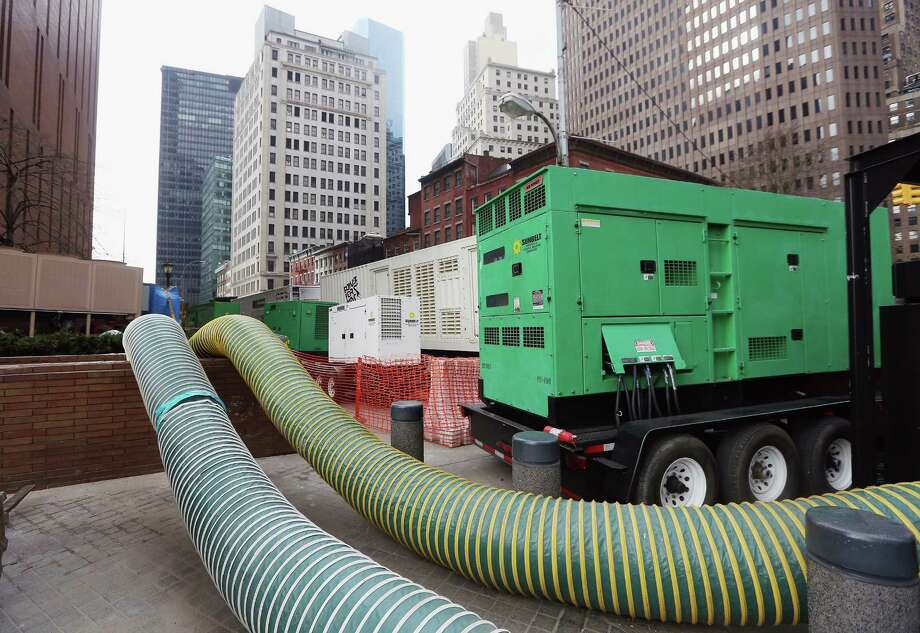 NEW YORK, NY - NOVEMBER 19:  Generators and tubes carrying hot air sit outside Financial District buildings that flooded during Superstorm Sandy on November 19, 2012 in New York City. Many of the office towers in the low lying Financial District which flooded remain closed due to damage to heating and electrical infrastructure.  Many other buildings in the area are being powered by generators. Photo: Mario Tama, Getty Images / 2012 Getty Images