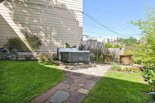 The backyard is fully fenced and includes a stone patio area, a good-sized yard and enough space for a fire pit or hot tub. Photo: Olga Soboleva