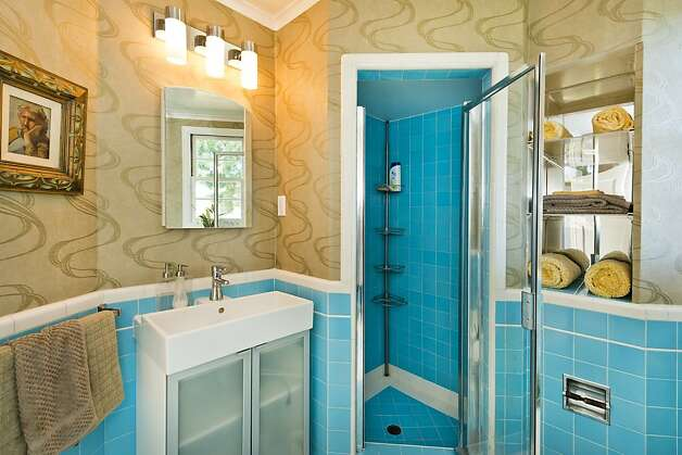 The downstairs full bathroom has blue tile and modern-print wallpaper. Photo: Olga Soboleva