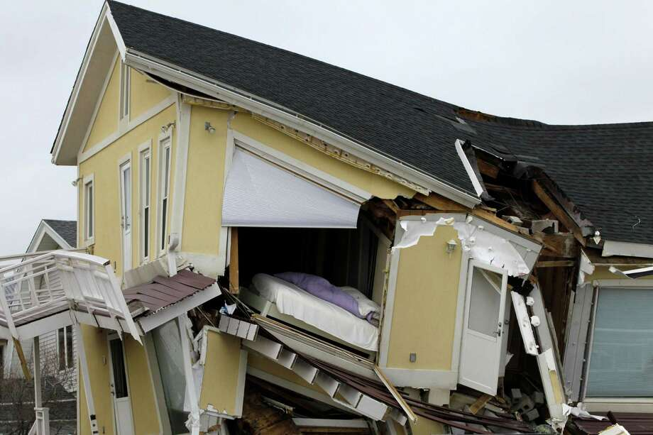 A bed sits precariously exposed in a partially collapsed home in the Belle Harbor neighborhood of the Rockaways, Monday, Nov. 19, 2012, in New York. The house is one of many deemed unsafe to enter or live in by the New York City Department of Buildings. Photo: Kathy Willens, AP / AP