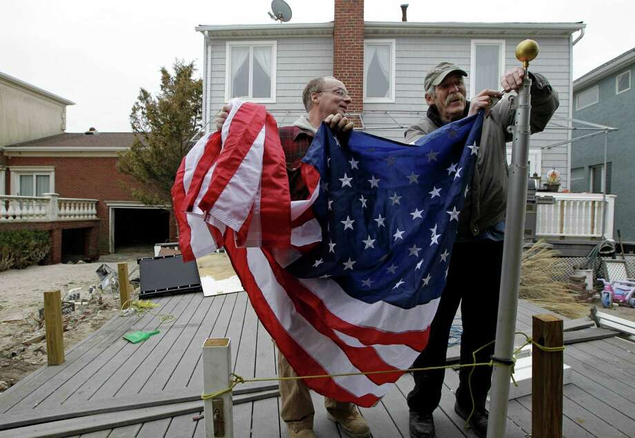 Evan Gray, left, helps his neighbor, retired firefighter Bill Connolly, 68, raise an American flag Connolly took down before Superstorm Sandy on a flagpole that was knocked down during the storm in the Belle Harbor neighborhood of the Rockaways, Monday, Nov. 19, 2012, in New York. Photo: Kathy Willens, AP / AP