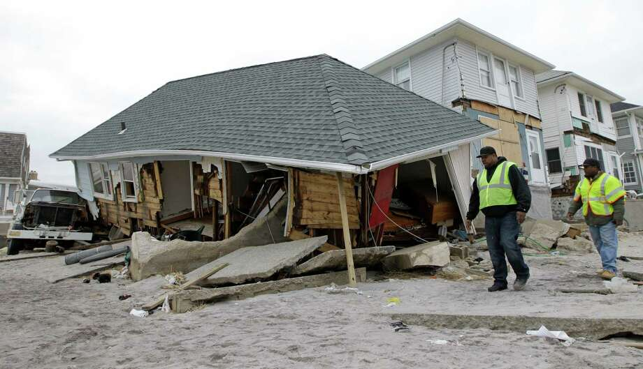 Utility workers walk past a badly damaged house in the Belle Harbor neighborhood of the Rockaways, Monday, Nov. 19, 2012, in New York. The house is one of 200 homes that has been designated unsafe by the New York City Department of Buildings. The city wants to demolish houses like this one because it says they are too dangerous to remain standing. Photo: Kathy Willens, AP / AP