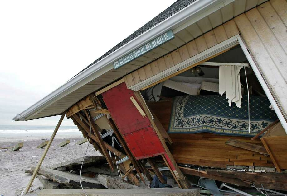The corner of a collapsed one-story house is held up by a wooden stick in the Belle Harbor neighborhood of the Rockaways, Monday, Nov. 19, 2012, in New York. The New York City Department of Buildings has put a red sticker on the house after ruling it unsafe to enter or live in. Photo: Kathy Willens, AP / AP
