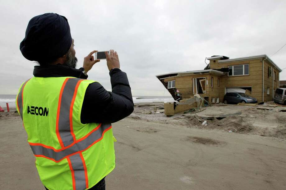 A structural engineer working for the New York City Buildings department snaps a personal photograph of a red-tagged, severely damaged house at the end of a block in the Belle Harbor neighborhood of the Rockaways in the Queens borough of New York, Monday, Nov. 19, 2012, in New York. New York's Department of Buildings plans to demolish 200 homes damaged by Hurricane Sandy and is inspecting 500 additional homes for possible demolition, according to the New York Times. Photo: Kathy Willens, AP / AP